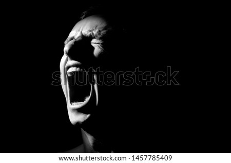 black and white photo on a black background, distorted face screaming Foto stock ©