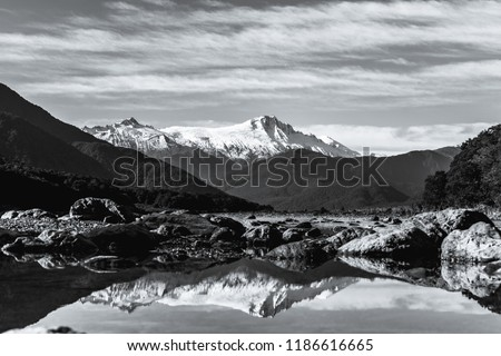 Black and white photo. Stunning landscpae of the reflection of the snow mountain on the river. Blue sky and some cloudy.