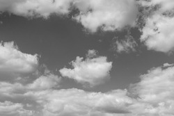 Black-and-white photo, white textured fluffy clouds in the sky.