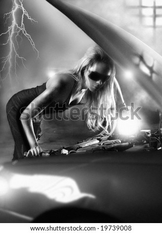 Black and white photo (with intentional film grain) of sexy blond woman under the hood of a car