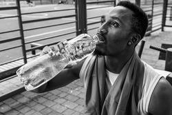 black and white photo, young muscular build man drinking water bottle after running, attractive athlete resting after outdoor workout, fitness and healthy lifestyle concept.
