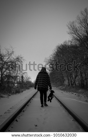 Black and white photograph of a  female walking away down the middle of railroad track in the snow while holding the paw of her Teddy Bear.