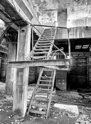 black and white photograph of staircase inside abandoned factory