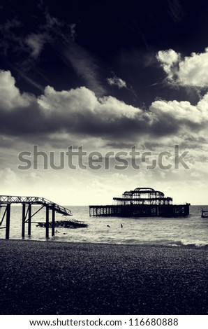 Black and white photograph of the remains of the west pier on brighton beach, Brighton, England, UK