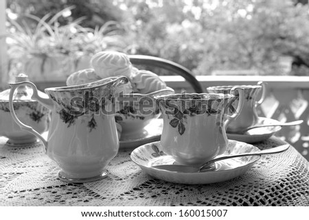 black and white photography image of beautifully laid tables outdoors for tea ceramic tea cups and dessert in the form of a marshmallow