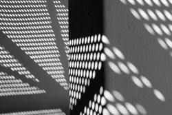 Black and white photography of modern architecture detail with shadows on the wall.