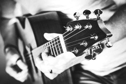 Black and White Photography of Musician Playing on Acoustic Guitar. Closeup with Shallow Depth of Field. Guitar Performance.