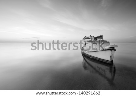black and white photography of sky and sea at sunrise with a little old boat abandoned in the Mar Menor, Spain