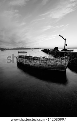 black and white photography of sky and sea at sunset with a little old fishing boat in the Mar Menor, Spain