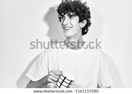 black and white photography.portrait of expressive young Italian teenager model boy posing for a fashion shooting, wearing a white shirt on white background and drinking a cup of tea/coffee
