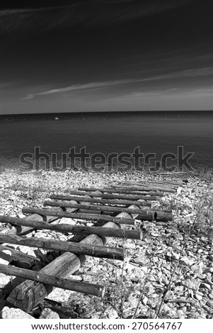 black and white photography. sea and the horizon and the sand and rocks and stairs