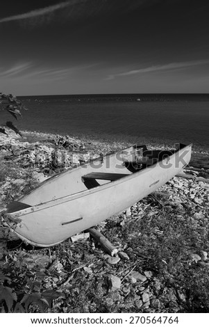 black and white photography. sea and the horizon and the sand and the rocks and the stairs and the boat