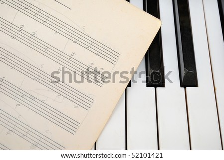 Black and white piano keyboard with old music sheet. For concepts like music and creativity.