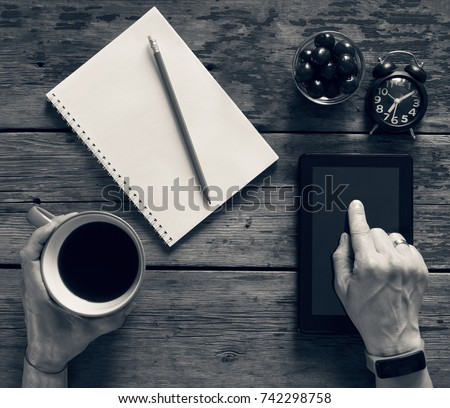Black-and-white picture. Freelancer works with a tablet computer at home at table,  open notepad, a pencil, clock. In his hand a cup of coffee. concept: work outside office, freelancing, remote work