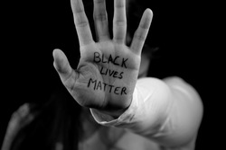 Black and white picture of a Caucasian girl showing support to the Black Lives Matter movement.