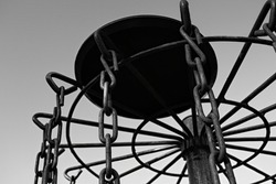 Black and white picture of a disc golf disc on top of a disc golf basket.
