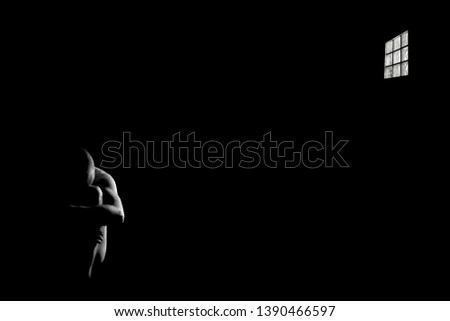 Black and white picture of a naked man sitting on the floor of a black room, holding his legs with his arms, partially lit. The room has a little window with bars.