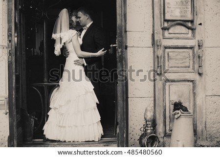 Black and white picture of a wedding couple standing in the old entrance