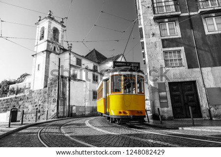 Black and white picture of a yellow tram on the streets of Lisbon, Alfama, Portugal near Santa Luzia church