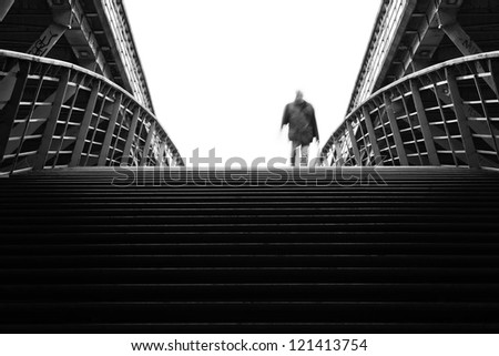 black and white picture of an unrecognizable man walking on a pedestrian bridge
