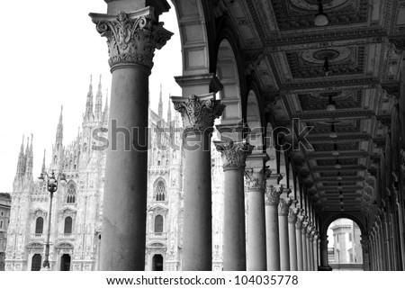 Black and white picture of ancient arcade and gothic cathedral of Milan, Lombardy, Italy