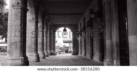 Black and white picture of building corridor with columns in old havana - stock photo