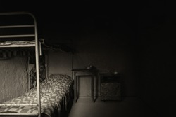 Black and white picture of dark empty prison cell with iron bunk bed and bedside table with aluminum dishes