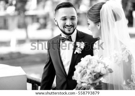 Black and white picture of handsome bearded groom admiring pretty bride