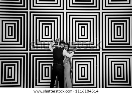Black and white picture of Indian wedding couple standing before a mosaic wall