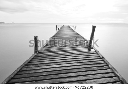 black and white picture of old bridge to the sea.