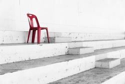 black and white picture of stadium seat with only one red