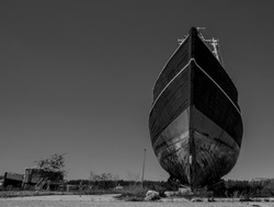 Black and White Picture. Old boat stands on land and rots. The boat would be decommissioned. the rusty paint peels off
