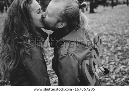black and white picture. Two young lovers and beautiful people for a walk in the park. Autumn Love Story two. Woman and a man with a beard. Keep love in hands. Writing and love letters. I love you.