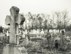 Black and white picture with a stone cross in a cemetery