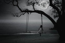 Black and white pictures. Little swings sitting by the sea on a full moon night like a lonely nature.