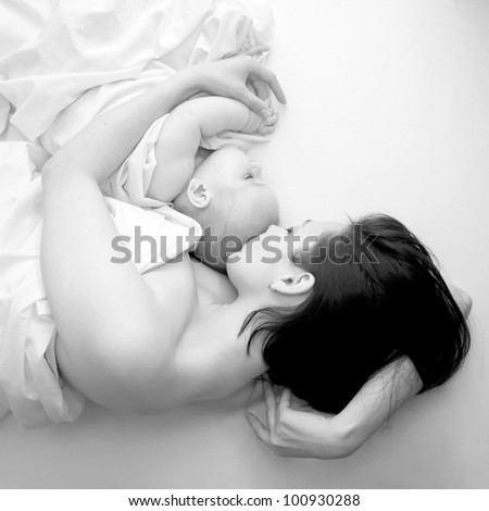 Black and white portrait - a young mother and her baby sleeping in bed. The symbol of maternal love, care, happiness and pacification