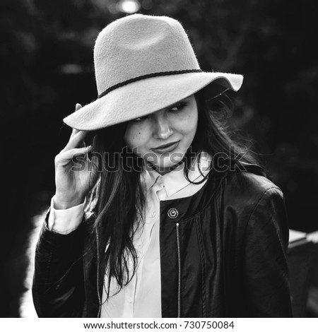 black and white portrait beautiful fashion girl in a hat on the street #730750084
