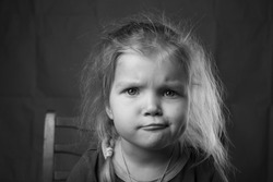 Black and white portrait Beautiful little girl with her hair and a skeptical pensive expression on her face, sitting on a chair in casual home clothes. Funny emotions of children. Thought and grin