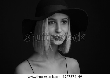 Black and white portrait blondes on a black background in a hat and Tank Top With Thin Straps. tight lips Stock photo ©