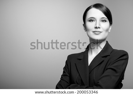 Black and white portrait of a beautiful elegant professional woman standing with folded arms in a stylish jacket looking at the camera with an enigmatic smile, with copy space