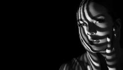 Black and white portrait of a beautiful young girl with a shadow pattern on the face and body in the form of stripes.
