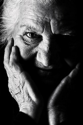 Black-and-white portrait of a calm senior woman looking at the camera. Over black background.
