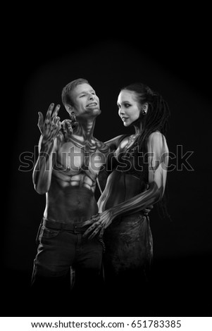 Stock Photo Black and white portrait of a character for computer game Bodyart cyborgs, man and woman with drawings on the body on a black background