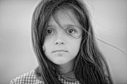 Black and white portrait of a child girl with sad expression. Hopeful concept