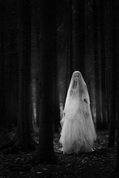 Black and white portrait of a ghost bride in a long white dress and veil standing in a gloomy dark forest.