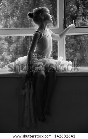 Black and white portrait of a little ballerina in pointes shoes is sitting on a Windowsill