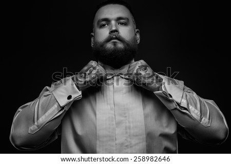 Black and white portrait of a man with beard and tattoos in white shirt and bow tie.