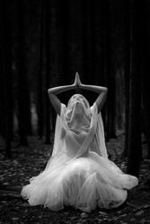 Black and white portrait of a mysterious woman bride in a gloomy forest in a prayer pose.