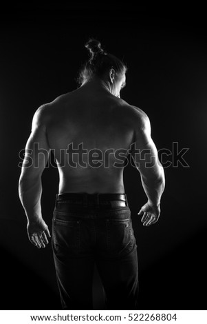 black-and-white portrait of a naked torso male bodybuilder athlete in the studio on a black background #522268804