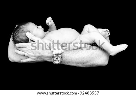 Black and white portrait of a newborn in father's, dad's hands